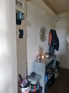 AVANT - l'entrée : compteur apparent, meubles disparates et faible lumière